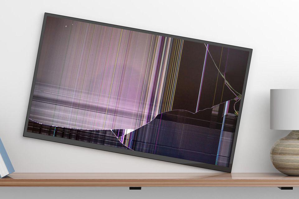 Kapputer Fernseher steht schief vor einer Wand