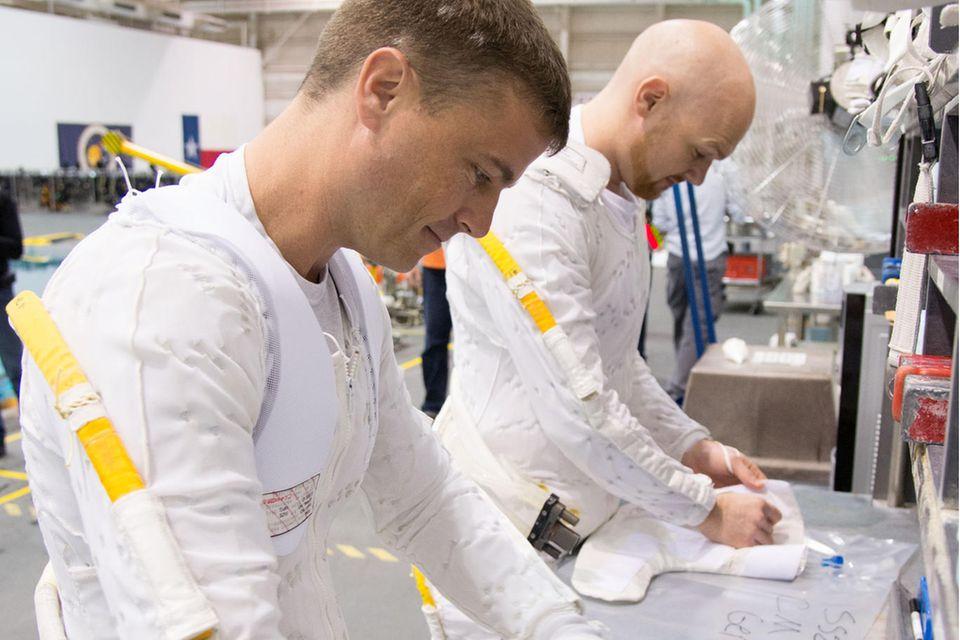 Die Besatzungsmitglieder der Expedition 40 (Sojus 39) Reid Wiseman (l.) und ESA-Astronaut Alexander Gerst (r.) tragen beim Training einen Kühlanzug. Der längere Aufenthalt von Menschen im Weltraum bringt so manches sehr irdisches Problem mit sich. Was tun mit der müffelnden Unterwäsche?