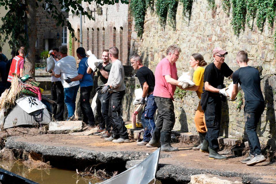Mit einer Menschenkette befördern Helfende in Bad Münstereifel Sandsäcke an das Ufer der Erft. In der Nacht zum 15. Juli 2021 verwüstete Hochwasser den historischen Kern der Stadt in Nordrhein-Westfalen. Straßen und Geschäfte wurden überflutet. Gas-, Strom und Telefonleitungen beschädigt