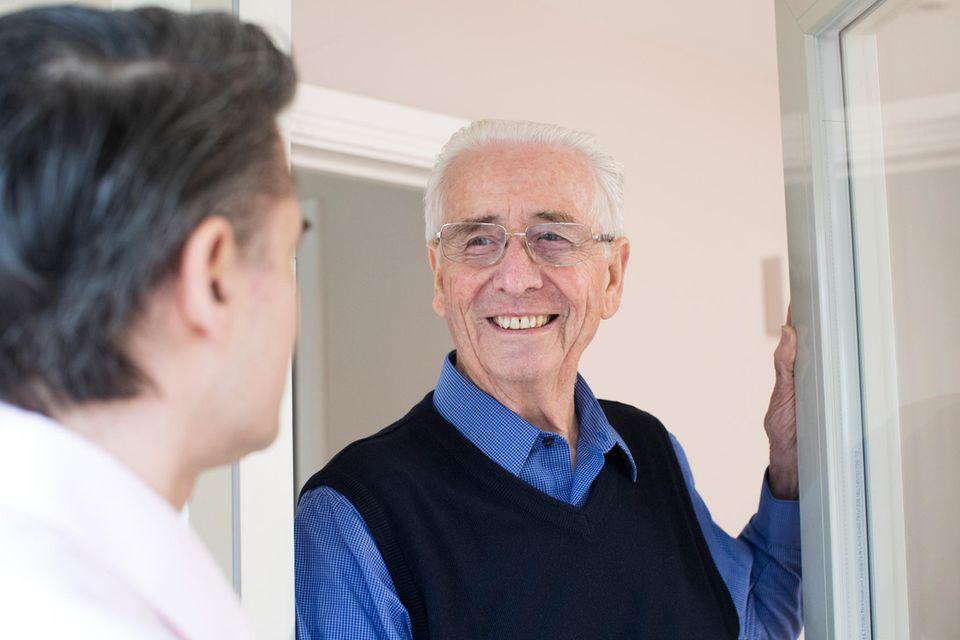 Senior mit Verkäufer an der Haustür