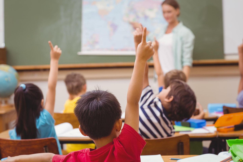 Schüler, die im Unterricht in der Grundschule die Hand heben