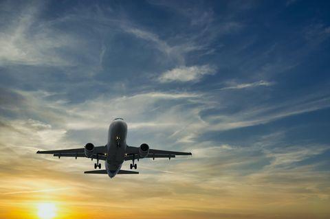 Ein Flugzeug fliegt am Himmel im Sonnenuntergang