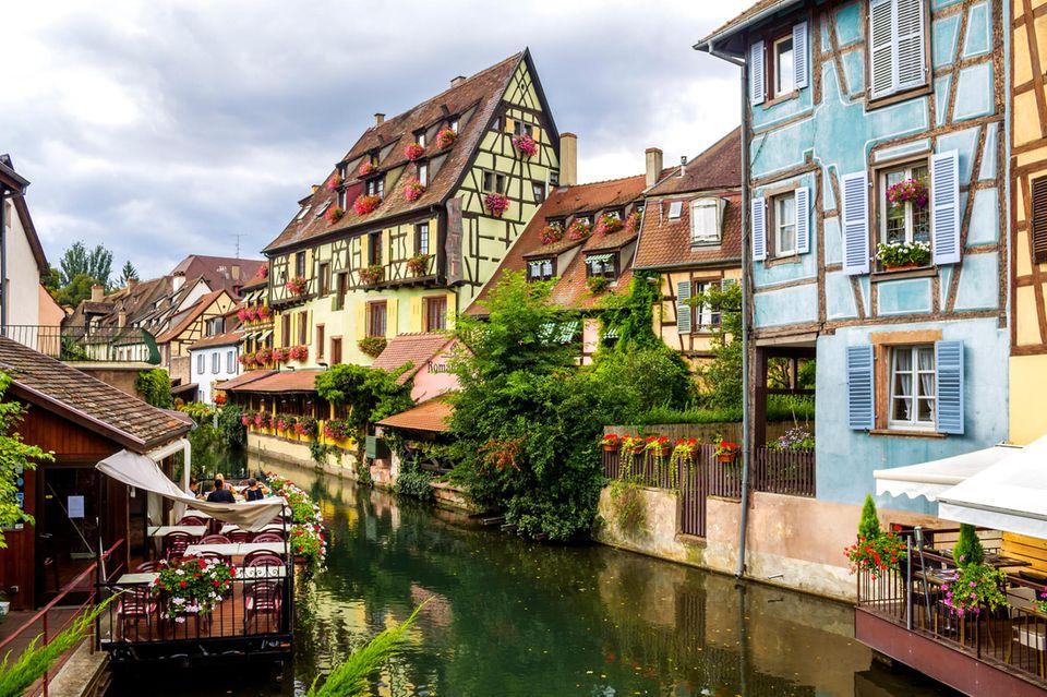 Bunte Fachwerkhäuser säumen das Flussufer in Colmar