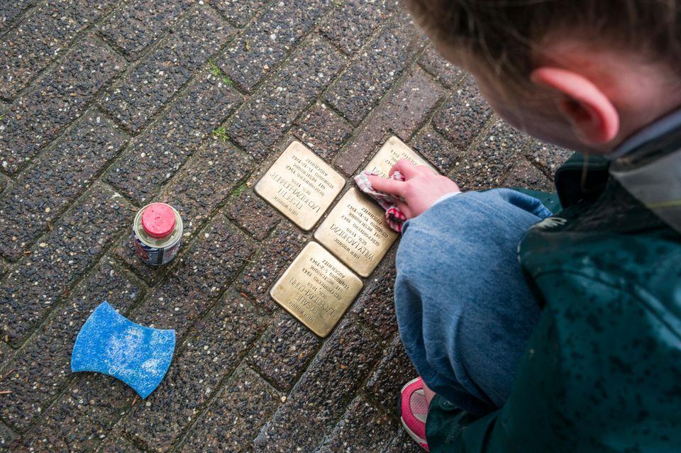 Vier Messingplatten im Boden erinnern an verschleppte Kinder, Frauen und Männer