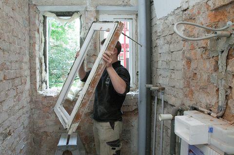 Mann setzt neues fenster in ein Haus ein