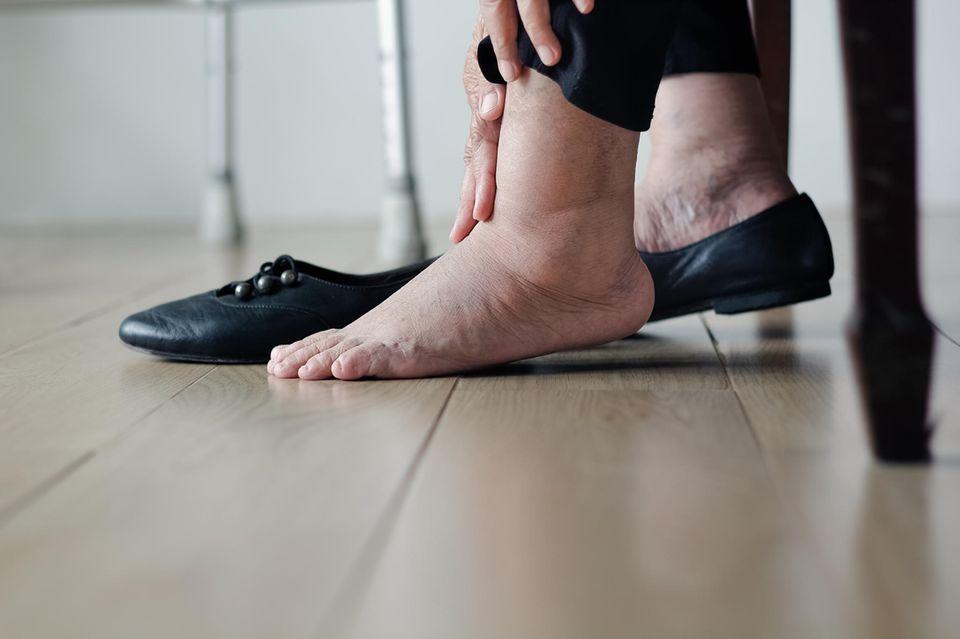Ältere Frau zieht mit geschwollenen Füßen Schuhe an