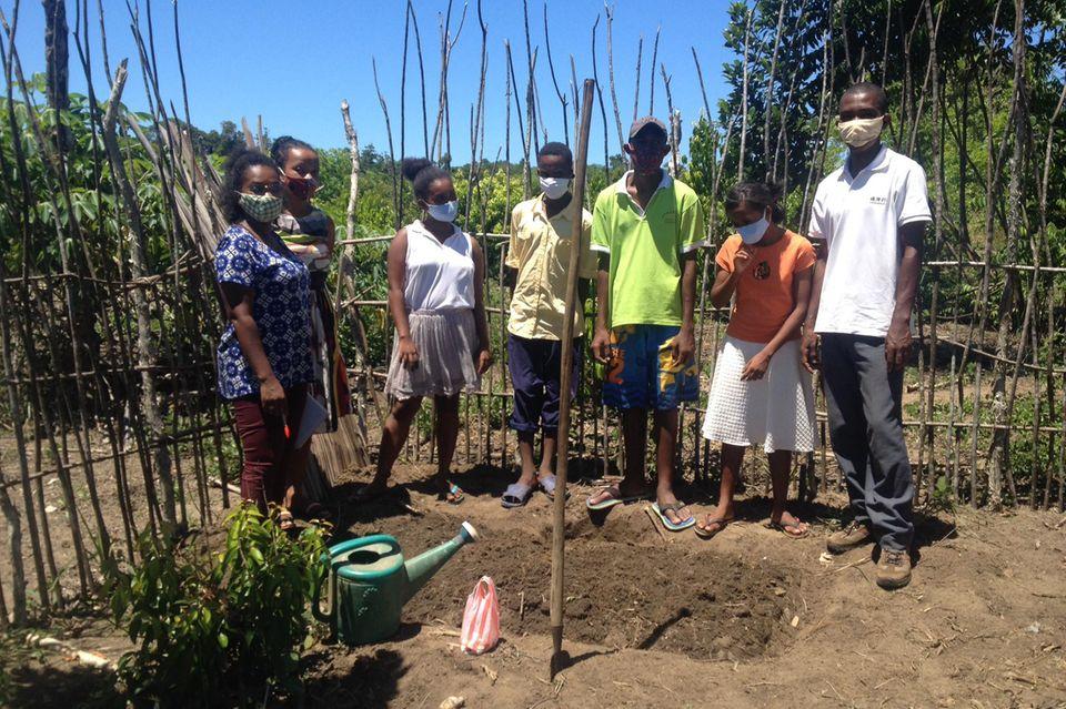 Evrard Benasoavina (rechts) und seine Assistentin Marie Olys (links) kompostieren mit Schülerinnen und Schüler ein Beet