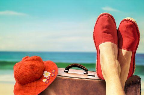 Frau legt ihre Füße auf einen Koffer am Strand