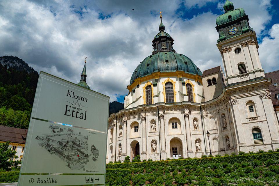 Kloster Ettal mit einem Hinweisschild im Vordergrund