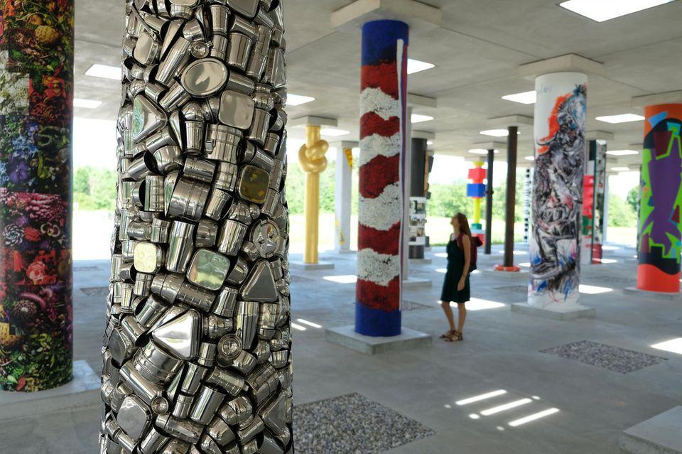 Frau schaut sich die Säulen des Kunstprojekts Projekt Stoa 169 an