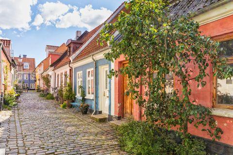 Gepflasterte Straße mit bunten Häusern in der Altstadt von Aalborg, Dänemark