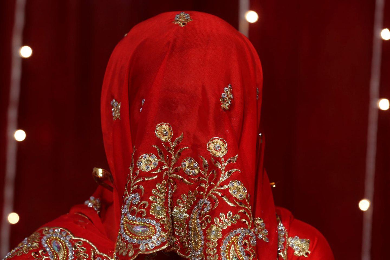 Eine indische Braut blickt durch ihren roten Schleier