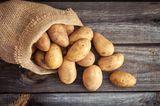 Frische Kartoffeln auf altem Sack auf Holzhintergrund