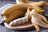 Bananen und Bananenscheiben auf einem Holzbrett