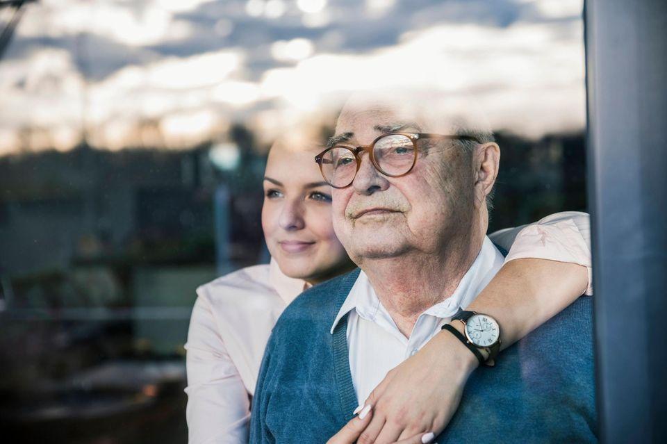 Frau umarmt ihren Vater und beide schauen aus dem Fenster