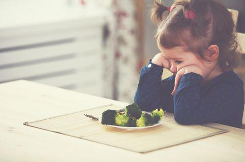 Mädchen sitzt vor Brokkoli und mag ihn nicht
