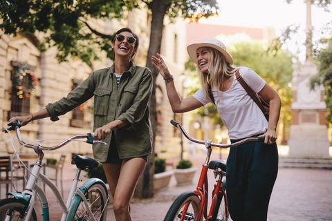 Frauen schieben Fahrräder durch die Stadt