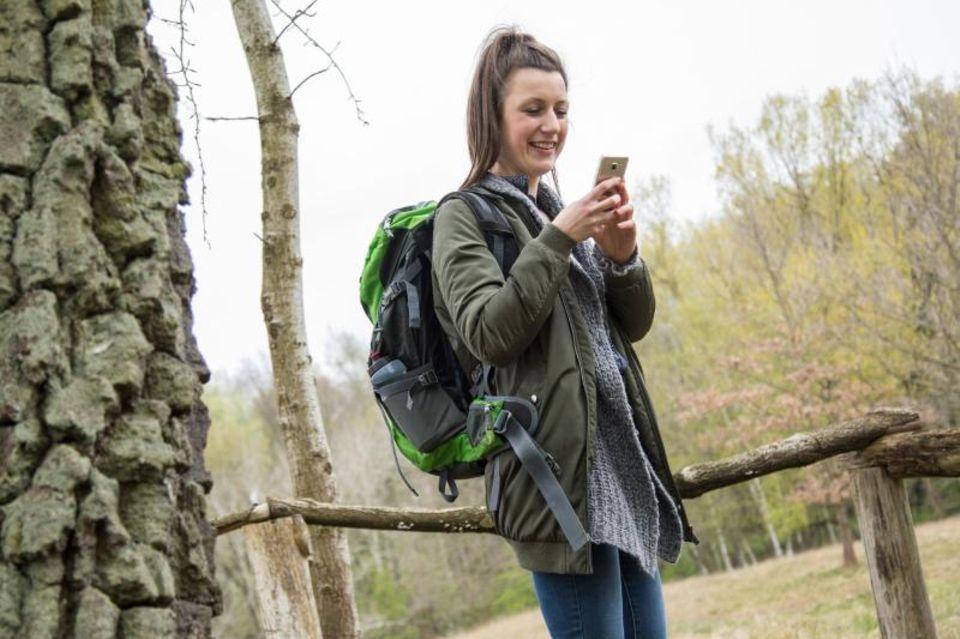 Frau schaut beim Wandern auf ihr Smartphone