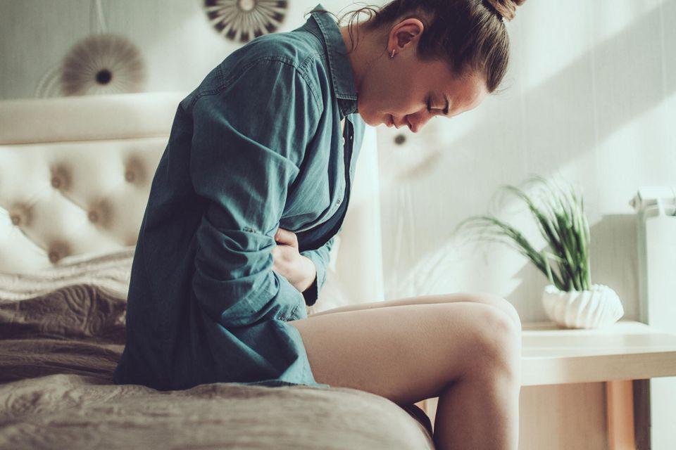 Junge Frau, die unter Menstruationsschmerzen leidet, sitzt auf der Bettkante