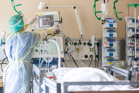 Eine Pflegerin versorgt eine im Koma liegende Corona-Intensivpatientin