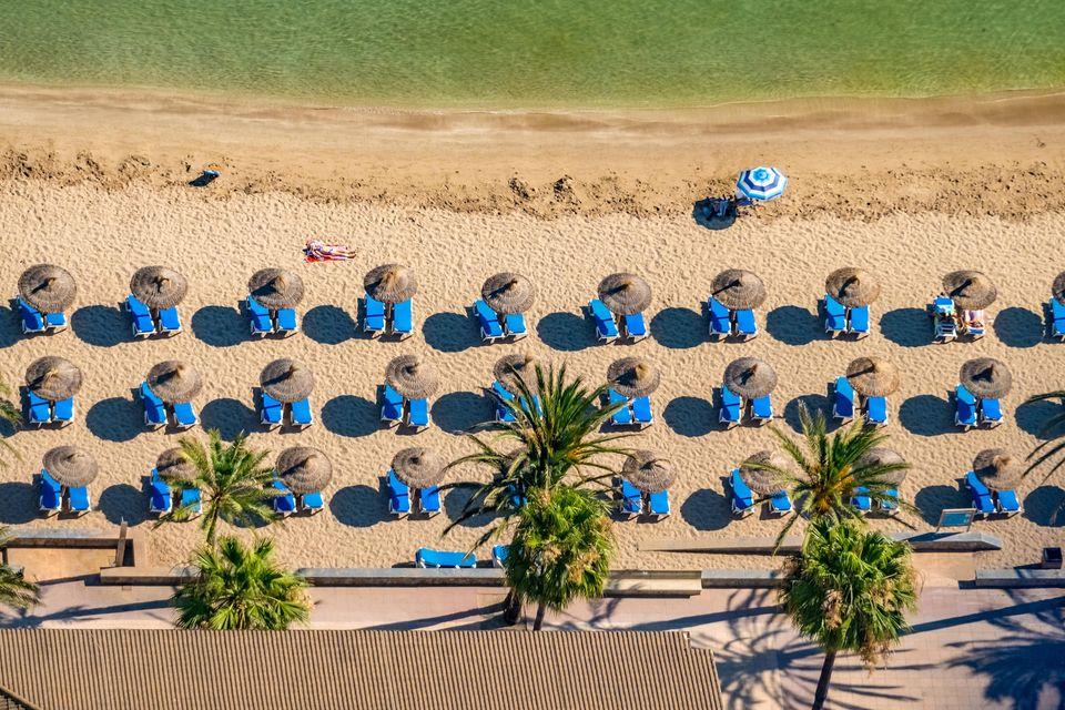 Luftbild von Sonnenliegen und Schirmchen am Strand
