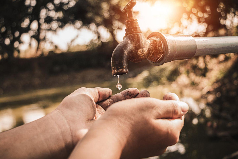 Hände unter einem Wasserhahn im Garten