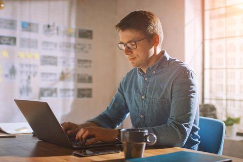 Mann sitzt im Homeoffice am Schreibtsich mit Laptop