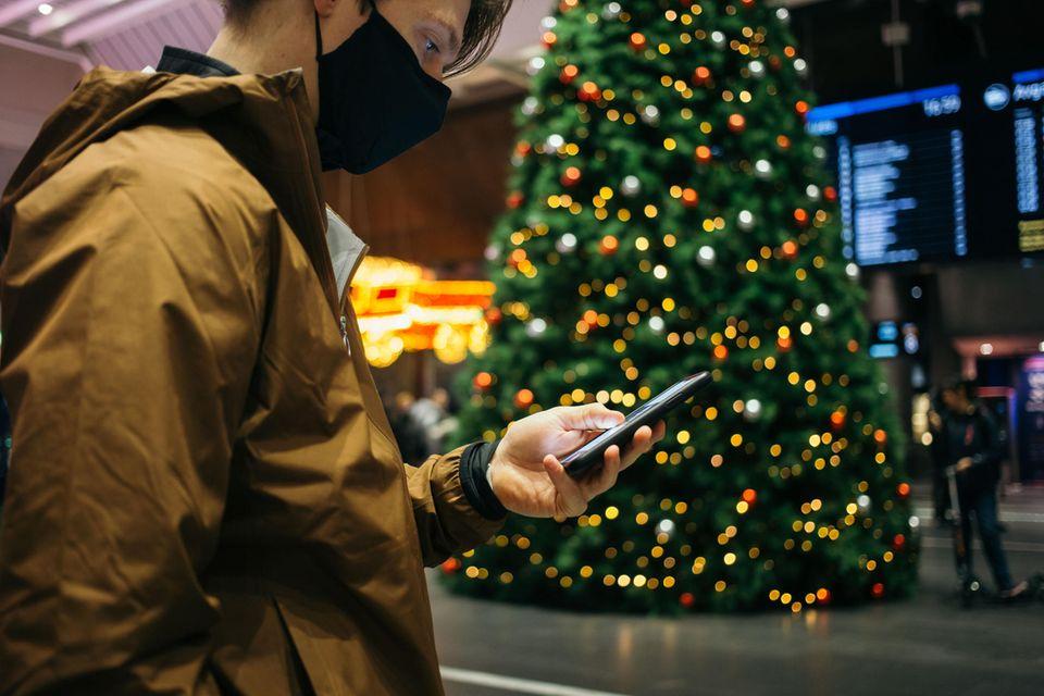 Mann blick am Bahnhof an Weihnachten auf sein Smartphone
